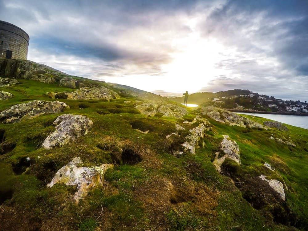 wide view of Dalkey Island in Ireland with moss and rock and the sun setting